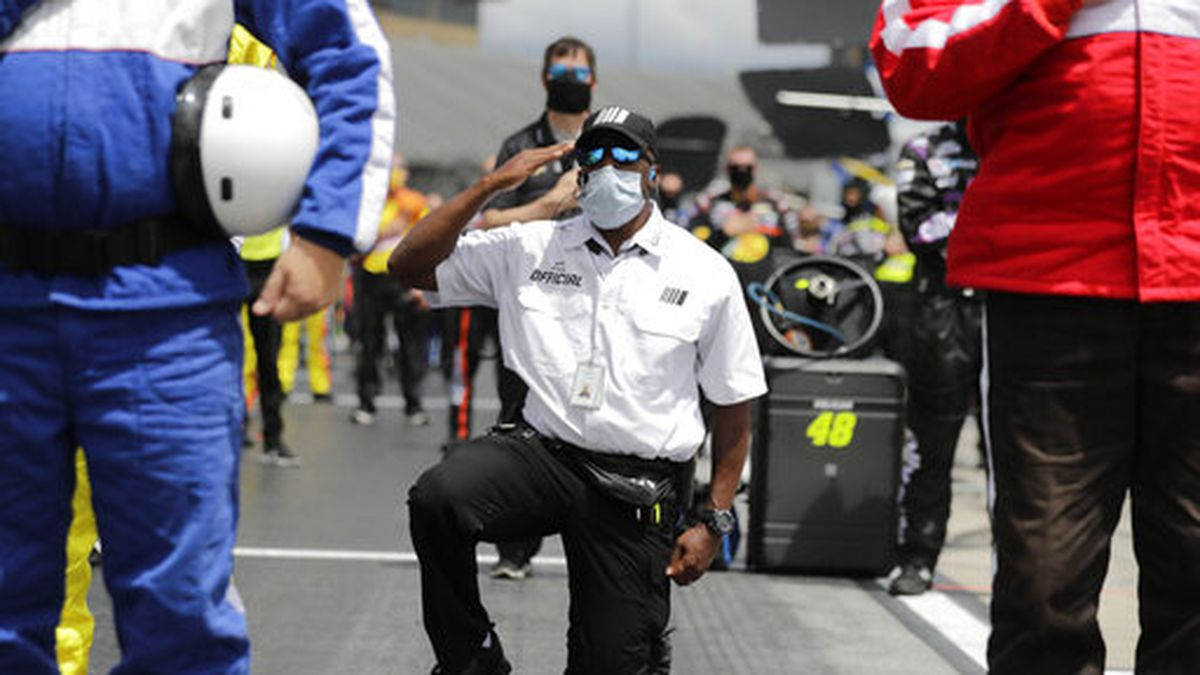 A NASCAR official kneels during the national anthem before a NASCAR Cup Series auto race at Atlanta Motor Speedway on Sunday, June 7, 2020, in Hampton, Ga. NASCAR paused before Sunday's Cup race at Atlanta Motor Speedway to acknowledge the country's social unrest. (AP Photo/Brynn Anderson)