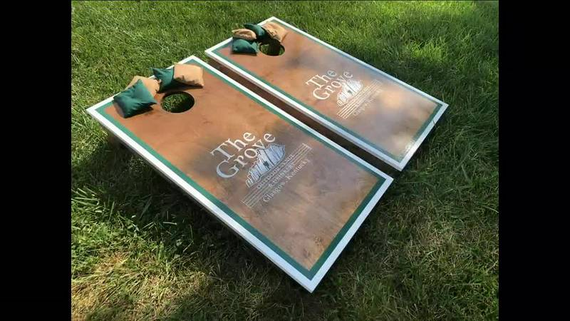 Zach and Alyssa Simpson make wooden cornhole boards with business and team logos or other...