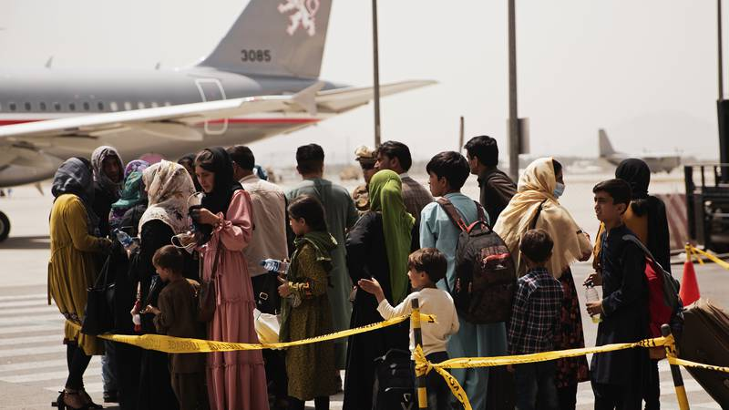 In this photo provided by the U.S. Marine Corps, civilians prepare to board a plane during an...