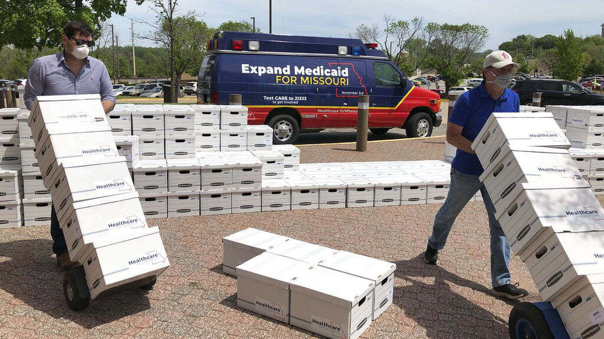 "FILE - In this May 1, 2020, file photo, campaign workers David Woodruff, left, and Jason White, right, deliver boxes of initiative petitions signatures to the Missouri secretary of state's office in Jefferson City, Mo. President Donald Trump is still trying to overturn ""Obamacare,"" but his predecessor's health care law keeps gaining ground in places where it was once unwelcome. Missouri voters this week approved Medicaid expansion by a 53% to 47% margin, making the conservative state the seventh to do so under Trump."