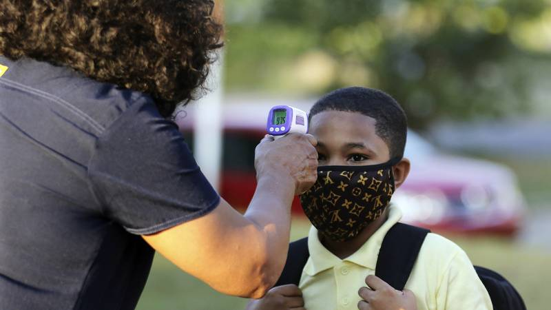 FILE - In this Monday, Aug. 24, 2020, file photo, fifth-grader Marcques Haley, gets his...