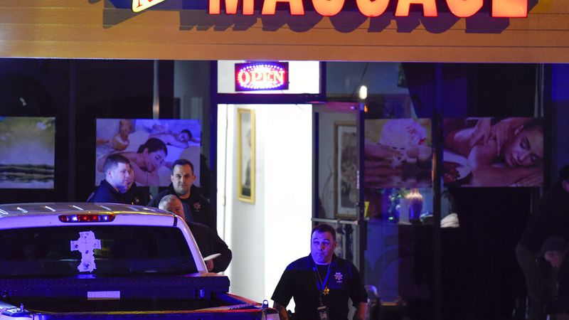Authorities investigate a fatal shooting at a massage parlor, late Tuesday, March 16, 2021, in...
