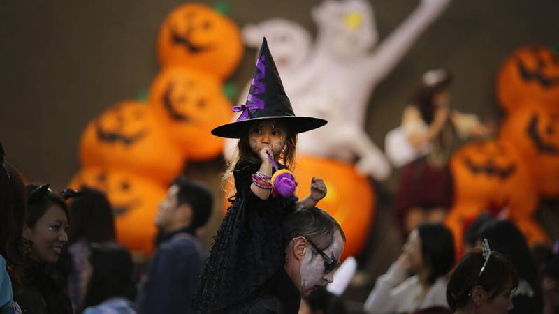 People in a disguise participate a Halloween costume festival in Tokyo, Saturday, Oct. 25,...