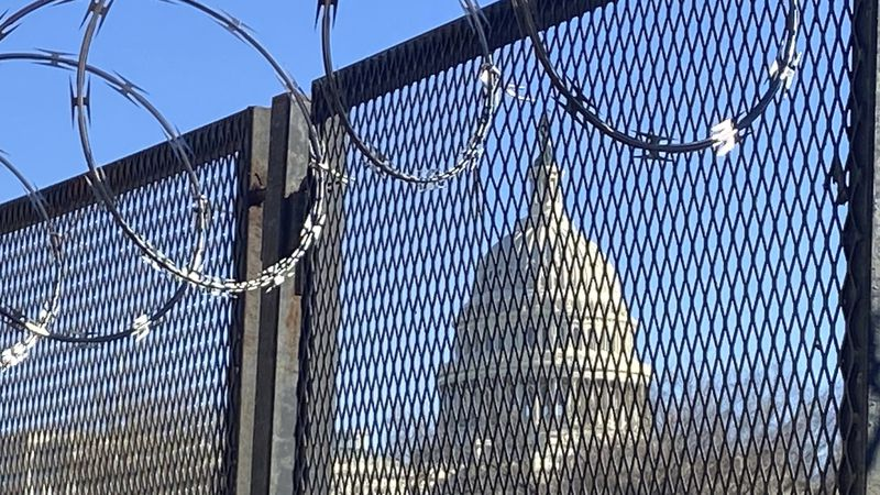 In this Saturday, Jan. 23, 2021 photo, riot fencing and razor wire reinforce the security zone...