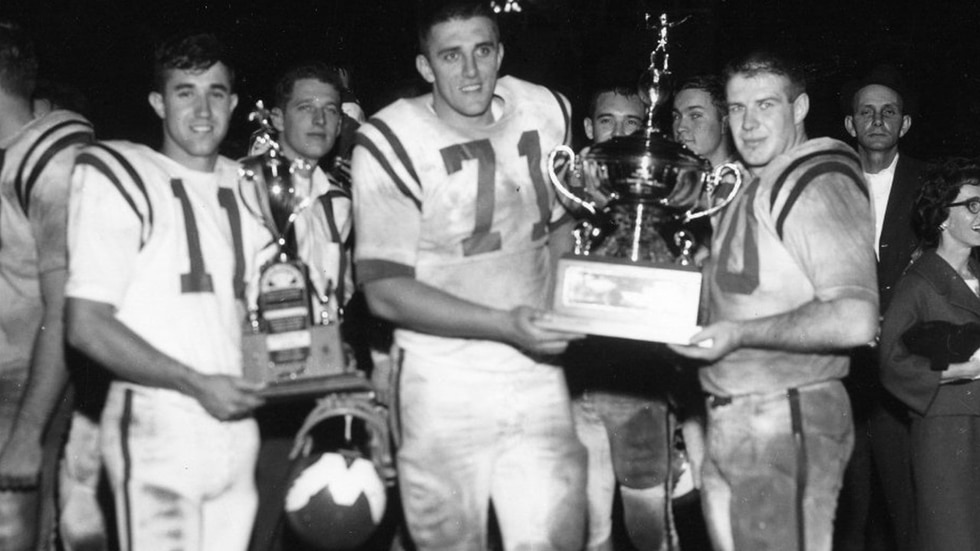 This classic photo – taken on the field following the 1963 Tangerine Bowl – features quarterback Sharon Miller (left), as well as team captains Harold Chambers (center) and Joe Bugel (right) hoisting the championship trophy. WKU defeated the US Coast Guard by a score of 27-0 to finish the season undefeated at 10-0-1.