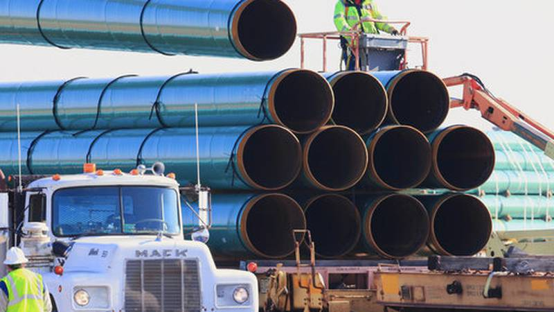 FILE - In this May 9, 2015, file photo, workers unload pipes in Worthing, S.D., for the Dakota...