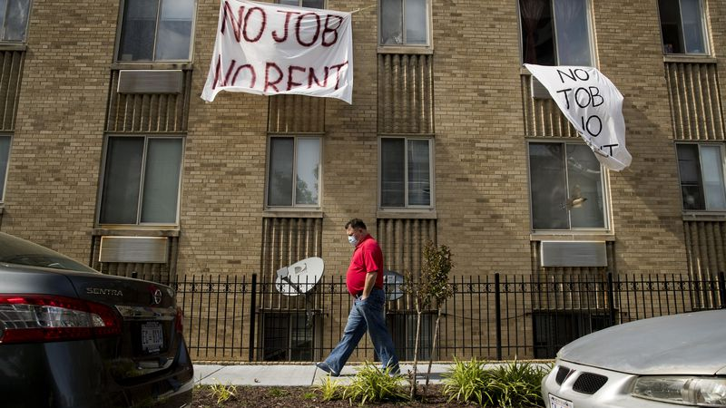 """FILE - In this May 20, 2020, file photo, signs that read """"No Job No Rent"""" hang from the windows..."""