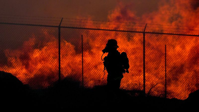 A firefighter walks past a wall of fire as multiple agencies battle a mulch and pallet fire...