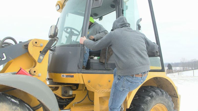 Farmers using equipment to plow unattended backroads.