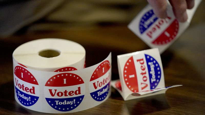 "An election worker prepares ""I Voted"" stickers at a polling place on Tuesday, Nov. 3, 2020, in..."