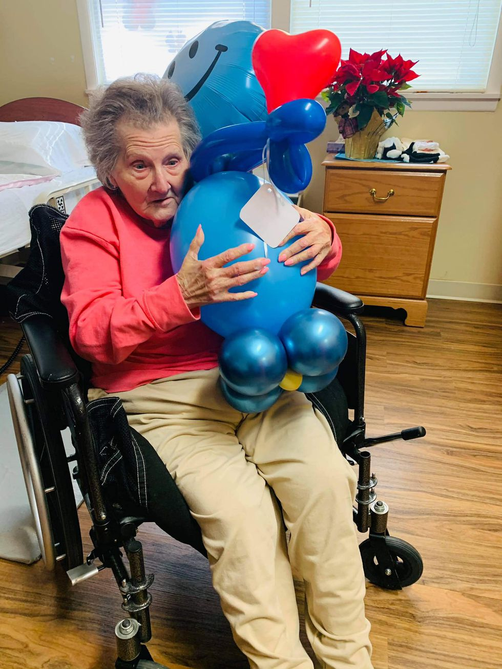 "Senior citizen poses with her ""balloon buddy."""